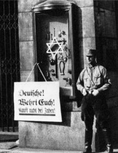 Boicot antisemita contra negocio judeo-alemán (Tietz, Berlín), marcado por los nazis con estrella judía junto a la cual figura un cartel con la inscripción «¡Alemanes! ¡Defendeos! ¡No compréis de los judíos!» Antisemitismo nazi, 1933.