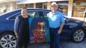 Gerry Montes con un cuadro de Ferdie Pacheco