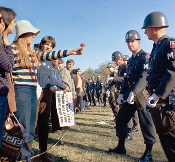 Una manifestante ofrece una flor a un guardia de la policía militar frente al Pentágono (Wikimedia).