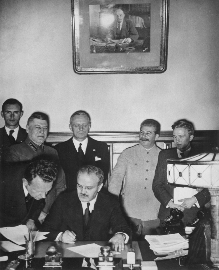 Firma del pacto Ribbentrop-Mólotov. El que está a punto de firmar es Mólotov, y detrás está Ribbentrop (con los ojos cerrados) y Stalin a su izquierda.