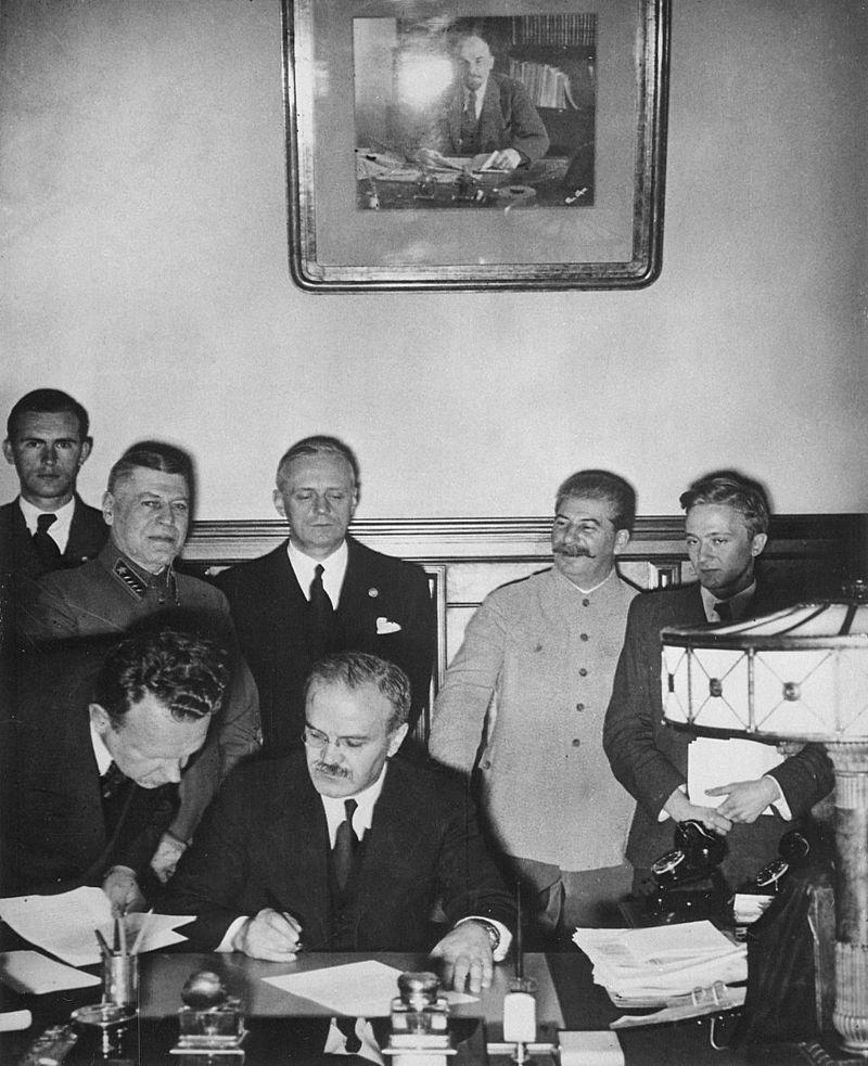 Pacto germano-soviético. Molotov en primer plano. Ribbentrop detrás junto a Stalin (agosto 1939) (Wikimedia).