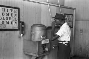 Afroamericano bebiendo de una fuente asignada a negros a mediados del siglo XX (Wikimedia).