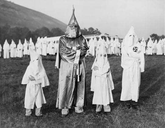 Dos niños vestidos con prendas asociadas al Ku Klux Klan acompañados por Samuel Green, poseedor del título de Gran Dragón, en Georgia, el 24 de julio de 1948 (Wikimedia).