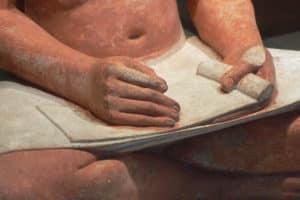 Detalle de El Escriba sentado, con un rollo de papiro. Escultura en piedra caliza. 2480-2350 a. C. Museo del Louvre, París (Wikimedia).
